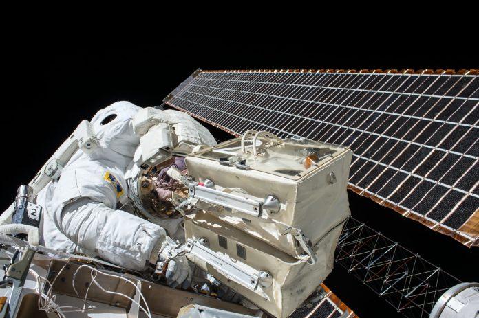 Astronaut repairing satellite