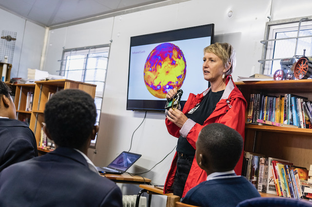 Judi Sandrock demonstrating the XinaBox ThinSat engineering model to the students that helped design it, Soneike High School, Cape Town.